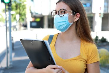 student wearing a mask holding a notebook